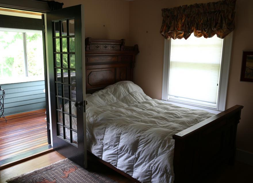 The guest bedroom offers its own three-season porch with a rich-toned hardwood floor and outdoor views.